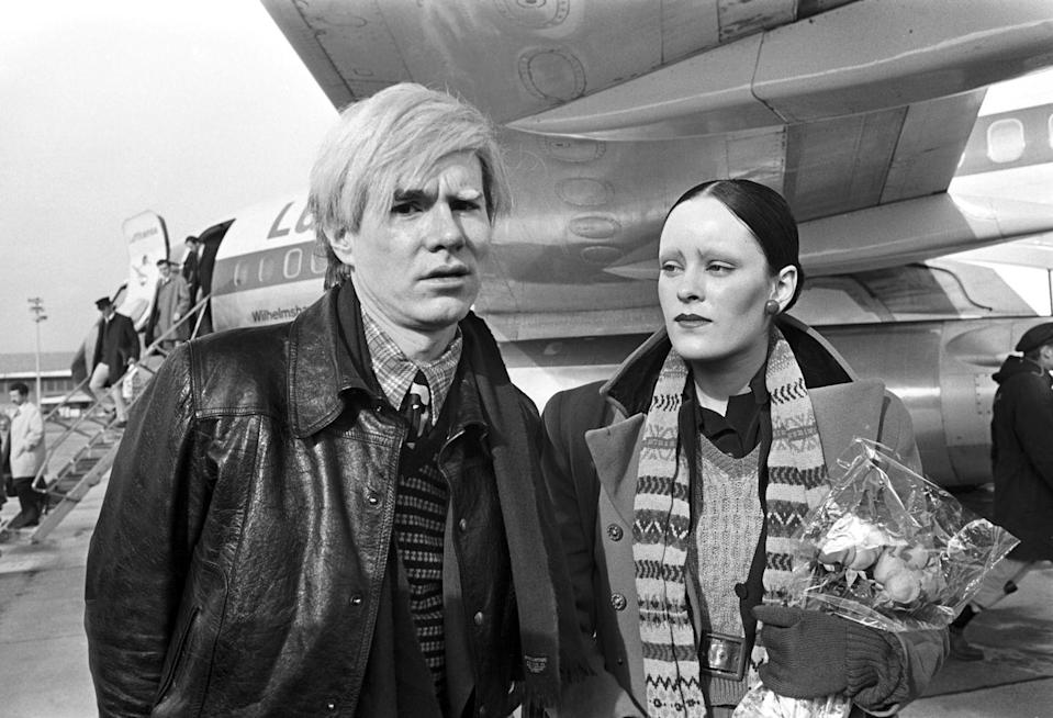 <p>Andy Warhol and actress Jane Forth are photographed upon their arrival in Munich, Germany in 1971. Warhol was visiting for the premiere of his film <em>Trash</em>. </p>