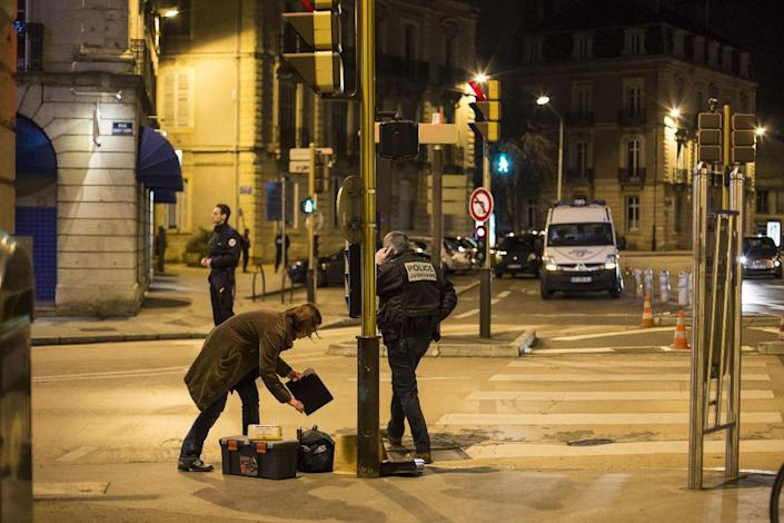 """Police collect evidence on December 21, 2014 in Dijon at the site where a driver shouting """"Allahu Akbar"""" (God is great) ploughed into a crowd injuring 11 people (AFP Photo/Arnaud Finistre)"""