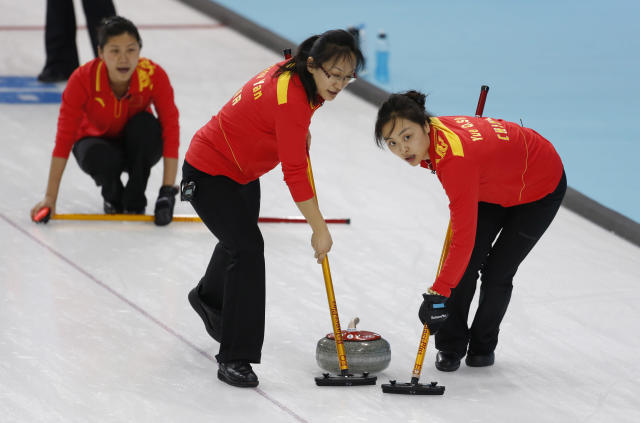 China's Zhou Yan, center, and Yue Qingshuang, sweep ahead of the rock thrown by Liu Yin, background, in a game against Canada during women's curling competition at the 2014 Winter Olympics, Monday, Feb. 10, 2014, in Sochi, Russia. (AP Photo/Robert F. Bukaty)
