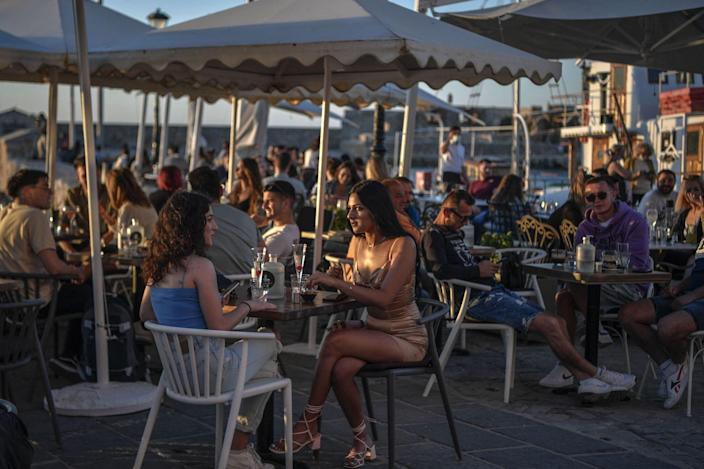 People sitting in a crowded outdoor bar/restaurant in Greece.