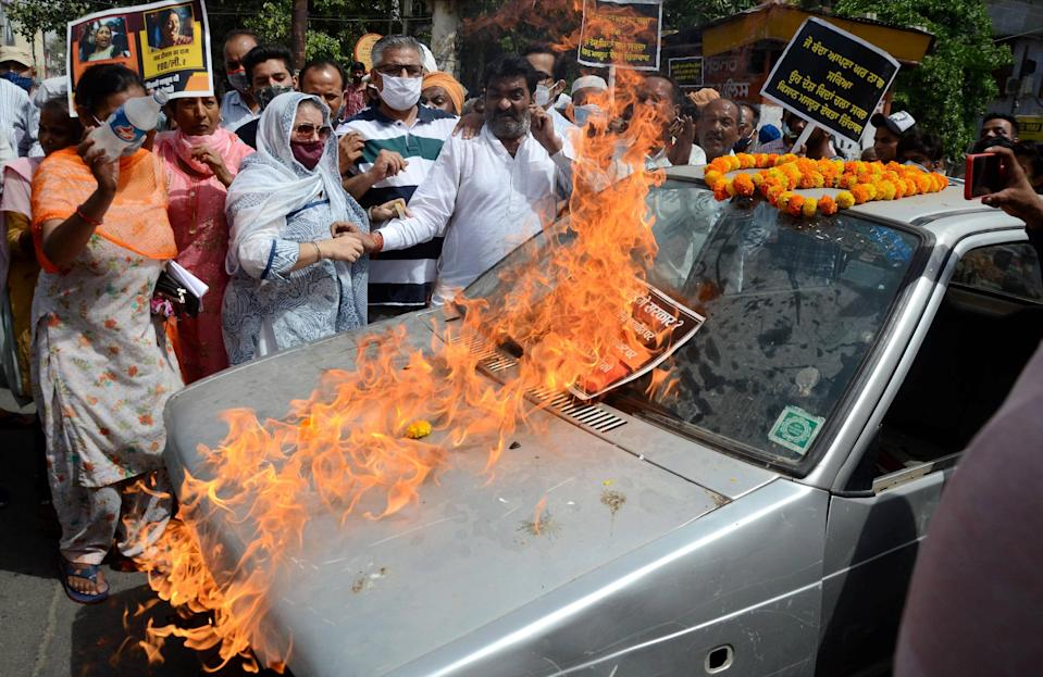 Congress workers put a car on fire during their protest against the central government over frequent hikes in the prices of petrol and diesel, in Amritsar on Friday, 11 June.