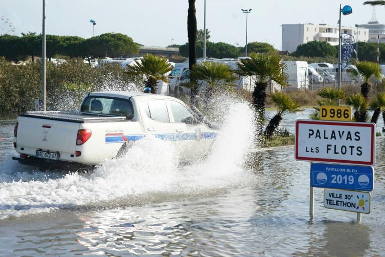 A police vehicle struggles through a flooded road in Palavas-les-Flots