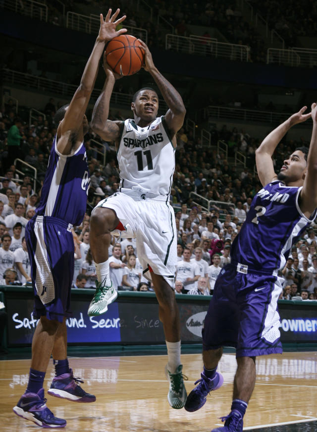 Michigan State's Keith Appling (11) drives between Portland's Kevin Bailey, left, and Alec Wintering during the second half of an NCAA college basketball game, Monday, Nov. 18, 2013, in East Lansing, Mich. Appling led Michigan State with 25 points in an 82-67 win. (AP Photo/Al Goldis)