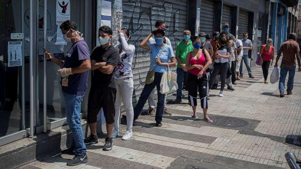 PHOTO: Dozens of people stand in a long line to stock up on medications and personal hygiene products at a pharmacy in Caracas, Venezuela, March 25, 2020. (EPA via Shutterstock)