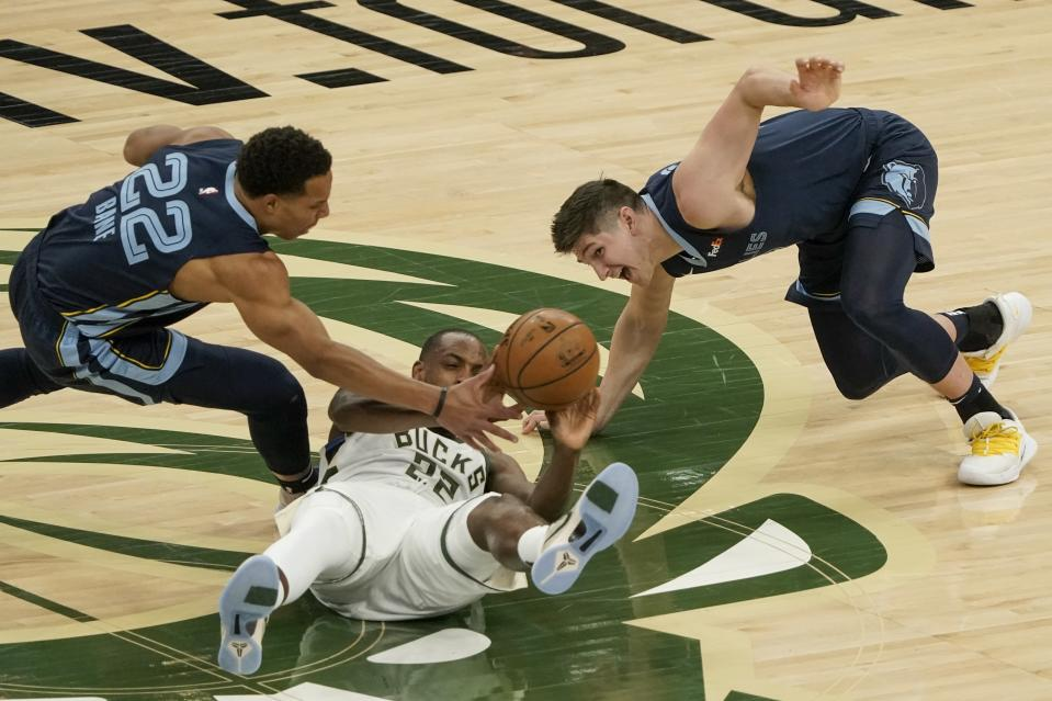 Milwaukee Bucks' Khris Middleton looks to pass with Memphis Grizzlies' Desmond Bane and Grayson Allen defending during the first half of an NBA basketball game Saturday, April 17, 2021, in Milwaukee. (AP Photo/Morry Gash)
