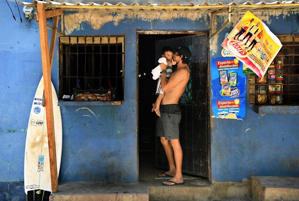 Surfer Bryan Perez holds his nephew outside his mother's store