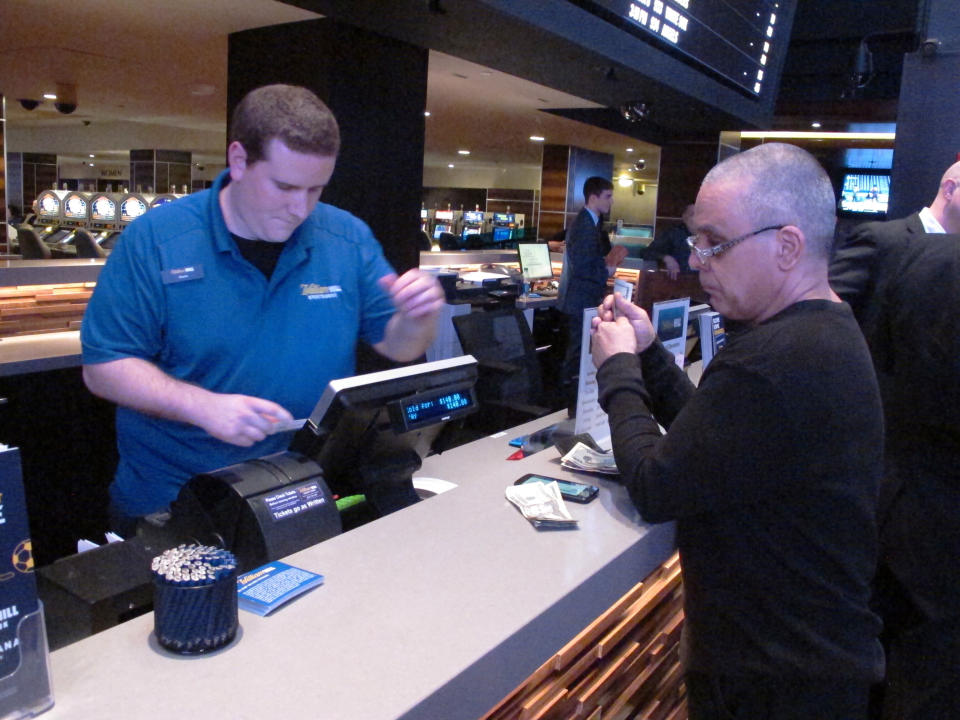 File- A gambler prepares to hand over cash at the sportsbook betting window inside the Tropicana casino in Atlantic City N.J. on March 8, 2019. On Sept. 14, 2020, New Jersey gambling regulators announced that New Jersey set a new national record for the amount wagered on sports in a single month in the U.S. with nearly $668 million bets on games. (AP Photo/Wayne Parry, File)