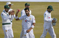 Pakistan's Hasan Ali, center, is congratulated teammates, who took five wickets during the third day of the second cricket test match between Pakistan and South Africa at the Pindi Stadium in Rawalpindi, Pakistan, Saturday, Feb. 6, 2021. (AP Photo/Anjum Naveed)