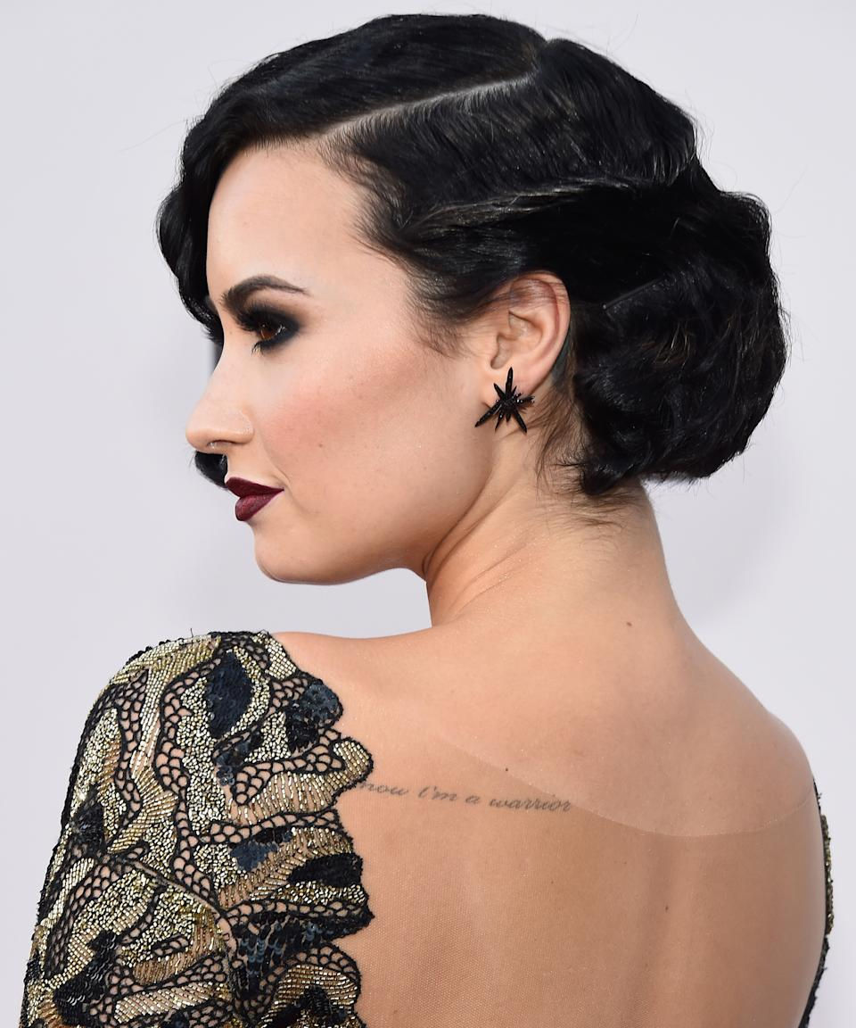 """<h3><strong>""""Now I'm A Warrior""""</strong></h3><br><br>In 2013, Lovato visited Bang Bang again to add """"Now I'm a warrior"""" to the back of her shoulder, a snippet of lyrics from the song """"Warrior"""" off her 2013 eponymous album <em>Demi</em>. """"[The tattoo] was kind of like a tribute to releasing the album as well as overcoming some really, really difficult things in my life,"""" she later explained on <em>Late Night with Jimmy Fallon.</em><span class=""""copyright"""">Photo: Frazer Harrison/AMA2015/Getty Images.</span>"""