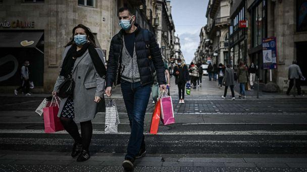 PHOTO: A man and a woman carrying shopping bags cross a street located in the mandatory face mask zone to limit Covid-19 infections in Bordeaux, Oct. 28, 2020, as France is set to put tough new measures in place. (Philippe Lopez/AFP via Getty Images)