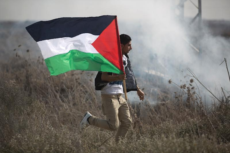 A Palestinian protestor runs with his national flag during clashes with Israeli forces near the Nahal Oz border crossing with Israel, east of Gaza City, on November 1, 2013 (AFP Photo/Mohammed Abed)