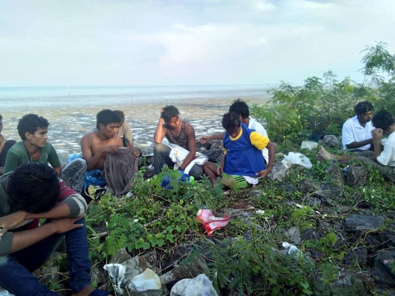 In this undated handout photo released April 8, 2019, dozens of people, believed to be Rohingya Muslims from Myanmar who were dropped off from a boat are pictured on a beach near Sungai Belati, Perlis, Malaysia. Malaysian police say a group of 41 Muslim Rohingya men have been detained in the northernmost state of Perlis, the second batch to have landed in the country in just over a month. (Malaysia Royal Police via AP)