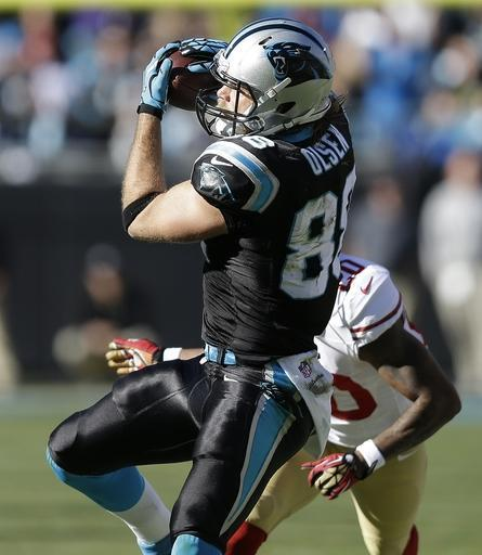 Carolina Panthers tight end Greg Olsen (88) makes a catch against San Francisco 49ers defensive back Perrish Cox (20) during the first half of a divisional playoff NFL football game, Sunday, Jan. 12, 2014, in Charlotte, N.C. (AP Photo/Gerry Broome)