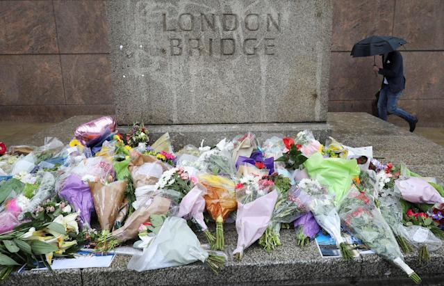 <p>A man walks past flowers and tributes left for the victims of the attack on London Bridge and Borough Market on a wet and windy morning in London, Britain, June 6, 2017. (Photo: Marko Djurica/Reuters) </p>