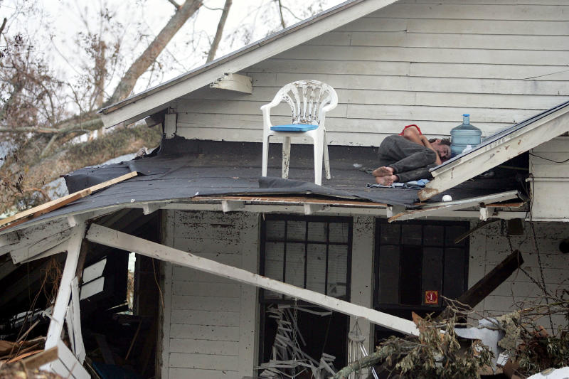 A man sleeps on the roof of his porch in Biloxi, Mississippi, on Sept. 1, 2005, after Hurricane Katrina destroyed his home. (Joe Raedle / Getty Images)