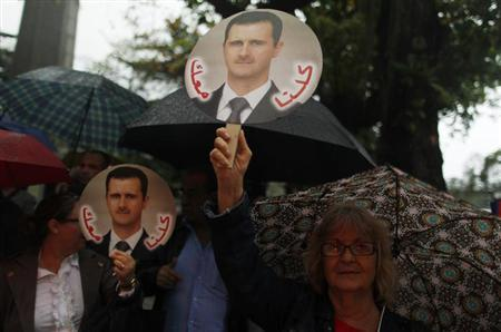 Protesters hold images of Syria's President Bashar al-Assad during a demonstration against possible U.S. military intervention in Syria in front of the U.S. embassy in Rio de Janeiro, September 4, 2013. REUTERS/Pilar Olivares