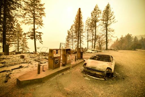 """A burnt car and a gas station remain visible on November 11, 2018 after the """"Camp"""" fire tore through the region near Pulga, east of Paradise, California"""