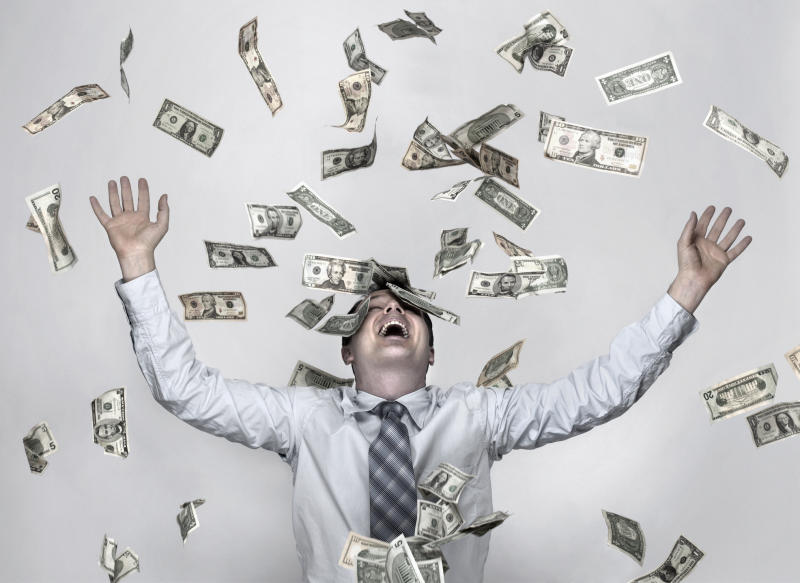 A man wearing a shirt and tie throws American dollar bills in the air. He is laughing.