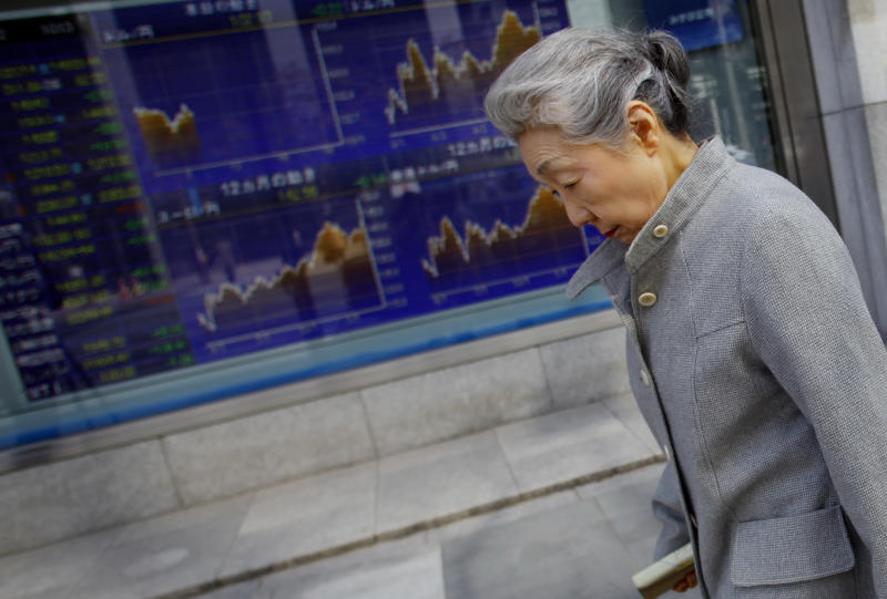 A woman walks by a securities firm in Tokyo, Wednesday, March 12, 2014. Asian stock markets sank Wednesday as recent falls in Chinese copper and iron prices added to jitters that the world's No. 2 economy is continuing to slow. (AP Photo/Junji Kurokawa)