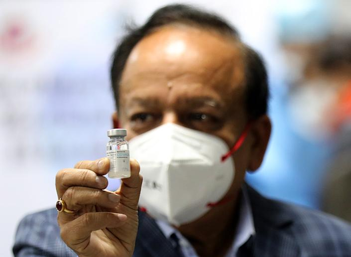 <p>India's health minister Dr Harsh Vardhan holding Bharat Biotech's Covid-19 vaccine, Covaxin, during the launch of the vaccination drive on 16 January</p> (EPA)