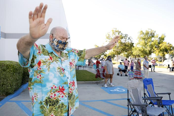 "Pastor Chris McPike and worshipers gather in the parking lot for a church service at Calvary Chapel in Temecula. <span class=""copyright"">(Christina House / Los Angeles Times)</span>"