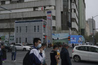 Pedestrians walk past a police station in Urumqi, the capital of China's far west Xinjiang region, on April 21, 2021. Four years after Beijing's brutal crackdown on largely Muslim minorities native to Xinjiang, Chinese authorities are dialing back the region's high-tech police state and stepping up tourism. But even as a sense of normality returns, fear remains, hidden but pervasive. (AP Photo/Dake Kang)