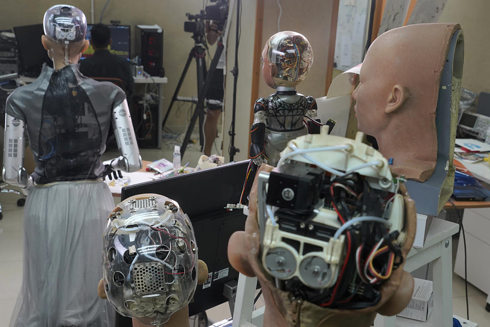 The head of Sophia, left, and other robotics show the inside content visually through the transparent skull at Hanson Robotics studio in Hong Kong on March 29, 2021. Sophia is a robot of many talents — she speaks, jokes, sings and even makes art. In March, she caused a stir in the art world when a digital work she created as part of a collaboration was sold at an auction for $688,888 in the form of a non-fungible token (NFT). (AP Photo/Vincent Yu)