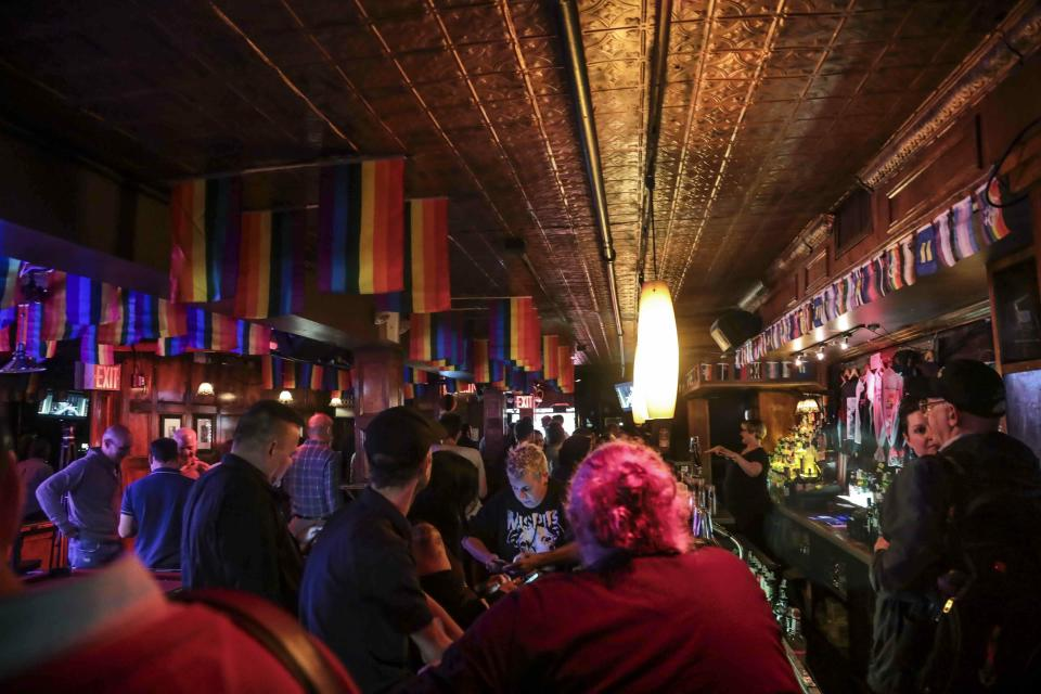 FILE - In this Monday, June 3, 2019, file photo, customers gather at the Stonewall Inn in New York. The Stonewall Inn's owners say they won't serve certain beers at the famous LGBT bar during Pride weekend to protest manufacturer Anheuser-Busch's political contributions to some politicians who have supported anti-LGBT legislation. (AP Photo/Bebeto Matthews, File)