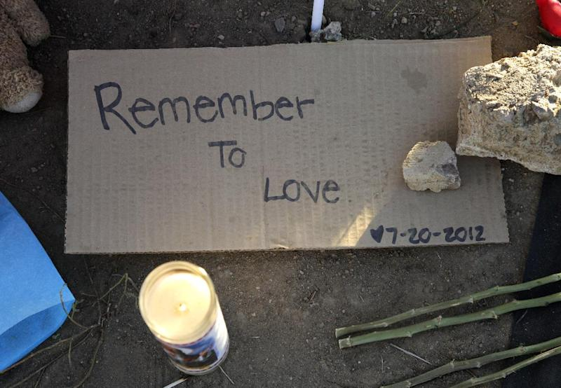 "A sign that reads ""Remember to Love 7-20-2012"" is shown at the memorial to victims of the Aurora, Colo., movie theater shooting, Friday, July 27, 2012. It was a week ago Friday that a gunman opened fire during a late-night showing of ""The Dark Knight Rises"" Batman movie, killing 12 and injuring dozens of others. Police have identified the suspected shooter as James Holmes, 24. (AP Photo/Ted S. Warren)"