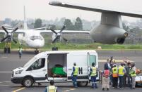 Officials prepare to load the bodies of the slain Italian ambassador to Democratic Republic of Congo Luca Attanasio and his Italian security Vittorio Iacovacci, at the Goma International Airport