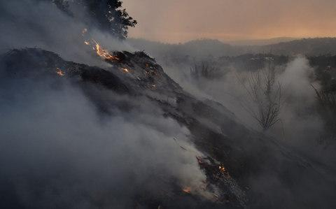 A hillside smolders at the Thomas Fire in Montecito - Credit: AFP