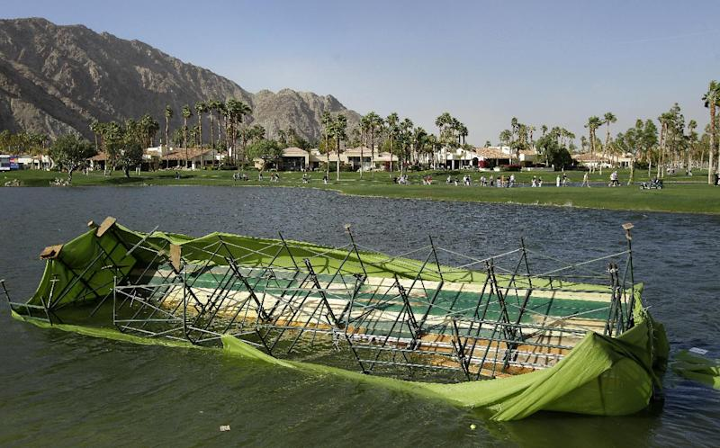 A scoreboard rest in the lake at the 18th hole as golf fans evacuate the Palmer Private Course at PGA West during the third round of the Humana Challenge PGA golf tournament Saturday, Jan. 21, 2012, in La Quinta, Calif.  Play has been suspended due to wind delay. (AP Photo/Ben Margot)