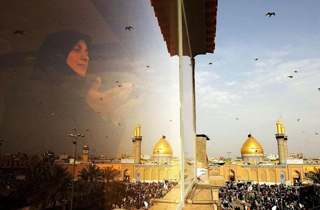 <b>KARBALA, IRAQ:</b> An Iraqi woman prays as Imam Abbas mosque is seen in the holy Shiite city of Karbala, south of Baghdad, Iraq. Karbala is famous as the site of the martyrdom of Hussein ibn Ali. The mosque, known to Shias as the Al-Abbas Mosque or Masjid al-Abbas, is the mausoleum of Al-Abbas ibn Ali, the martyr's loyal half-brother.