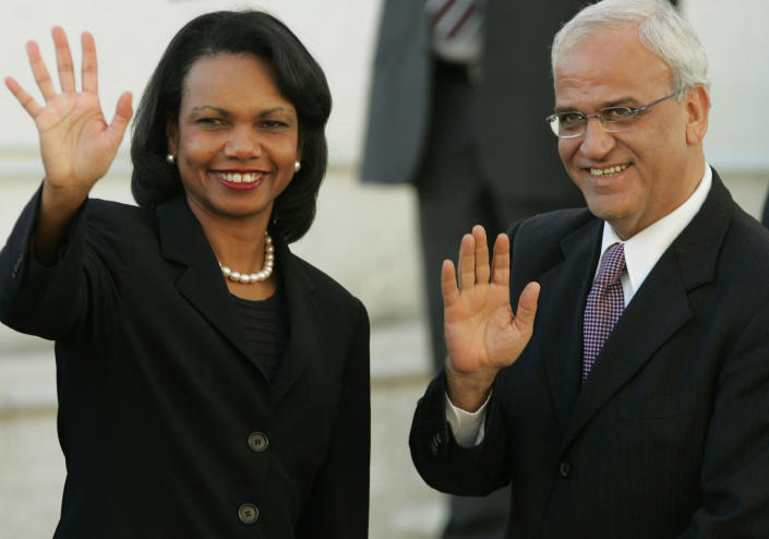 FILE- In this Oct. 4, 2006 file photo, then U.S. Secretary of State Condoleezza Rice, left, and Palestinian chief negotiator Saeb Erekat, wave as Rice arrives to Palestinian President Mahmoud Abbas' office in the West Bank city of Ramallah. Erekat, a veteran peace negotiator and prominent international spokesman for the Palestinians for more than three decades, died Tuesday, Nov. 10, 2020. He was 65. (AP Photo/Kevin Frayer, File)