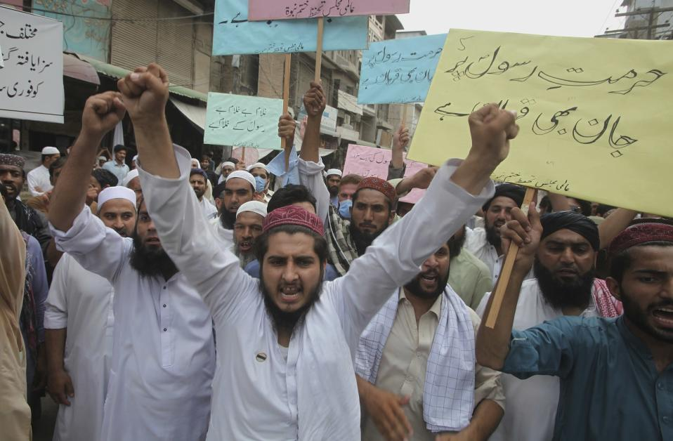 Supporters of a religious group chant slogan during a rally favoring the Khalid Khan, who gunned down Tahir Naseem in courtroom, in Peshawar, Pakistan, Friday, July 31, 2020. Naseem, a U.S. citizen, according to a U.S. State Department statement, was gunned down this week in a Pakistani courtroom while standing trial on a charge of blasphemy. The placard on right is read as 'we can die for honor of Prophet'. (AP Photo/Muhammad Sajjad)