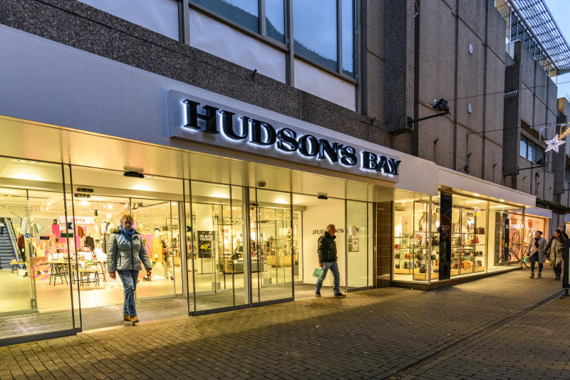 Hudson's Bay Company retail store in Zwolle during a cold winter evening. People are walking on the street and looking at the shop windows.