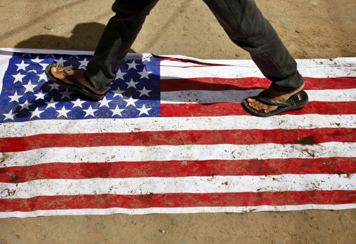 """An Indian man walks on an American flag in Hyderabad, India, during a protest against an anti-Islam movie called """"Innocence of Muslims,"""" which mocked Islam's Prophet Muhammad Friday, Sept. 14, 2012. (AP Photo/Mahesh Kumar A.)"""