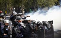 Thai policemen aim their weapons towards anti-government protesters during clashes near Government House in Bangkok February 18, 2014. At least three police officers were wounded as Thai authorities launched an operation to clear anti-government protesters from streets in Bangkok on Tuesday. REUTERS/Athit Perawongmetha (THAILAND - Tags: POLITICS CIVIL UNREST)
