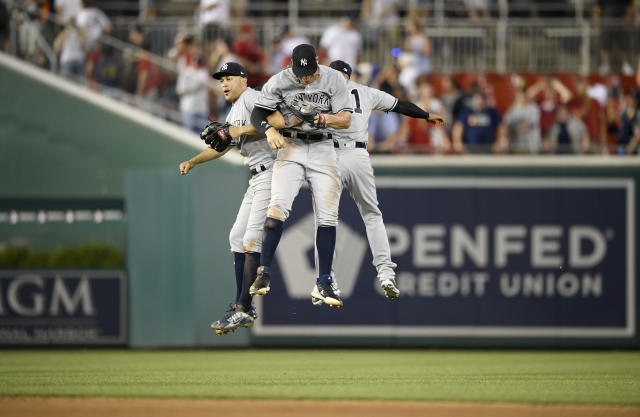 New York Yankees' Giancarlo Stanton, left, Aaron Judge, center, and Aaron Hicks, back left, celebrate after a baseball game against the Washington Nationals, Monday, June 18, 2018, in Washington. The Yankees won 4-2. (AP Photo/Nick Wass)