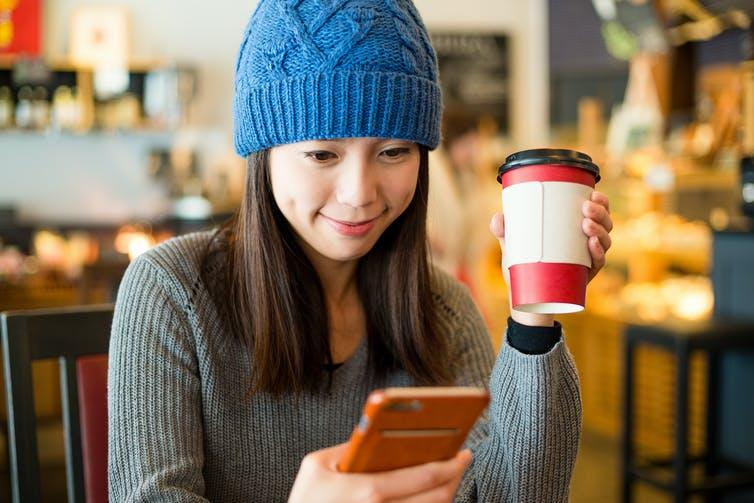 Woman holding phone and coffe cup sitting in a cafe.
