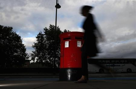A woman walks past a Royal Mail post box in central London, October 8, 2013. REUTERS/Andrew Winning