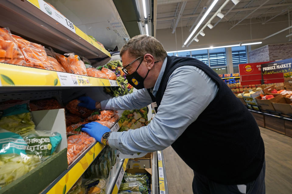 "In this Thursday, Feb. 4, 2021 photo, Joseph Lupo, an employee of the grocery chain Lidl, arranges carrots in the produce aisle at the grocery market where he works in Lake Grove, N.Y., after getting vaccinated against coronavirus earlier in the day. The German grocery chain is offering a $200 financial incentive all workers who get vaccinated against COVID-19. Lupo, a Lidl supervisor who fell ill with the virus in March, was elated to get his first vaccine dose. ""I never ever want to get COVID again, or see anybody else get it,"" said Lupo, 59. (AP Photo/Kathy Willens)"