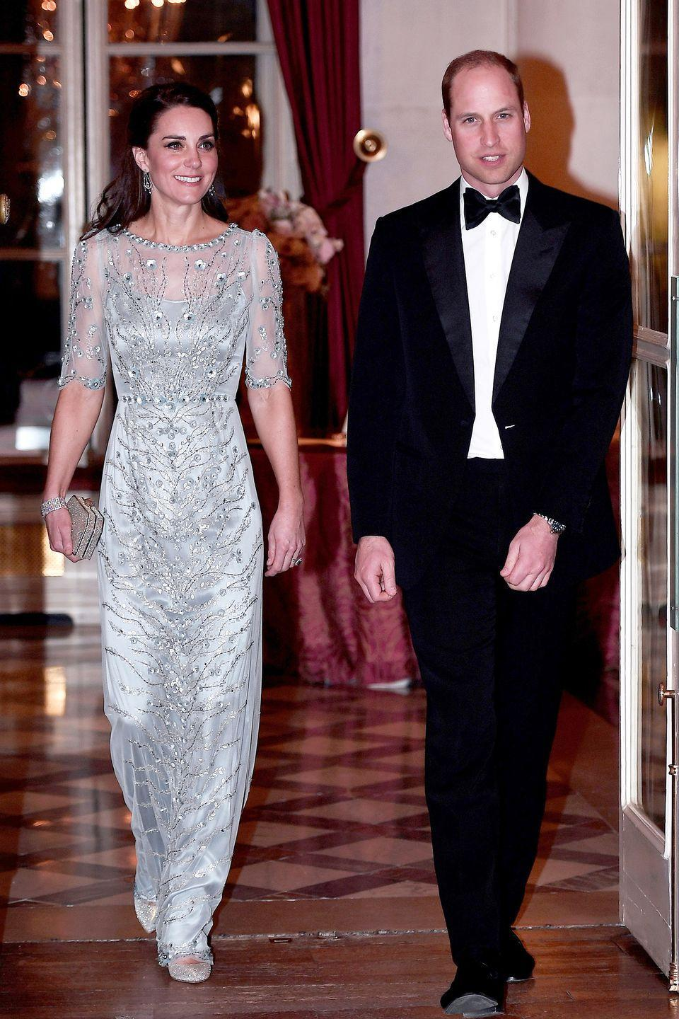 <p>In a beaded silver gown with a sheer top, bejeweled clutch, diamond bracelet, dangling earrings and shimmery pumps with Prince William at the British Embassy in Paris for a dinner.</p>