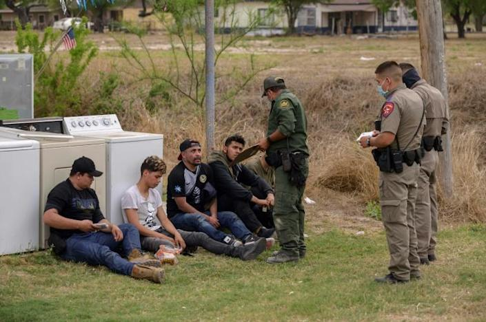 Young Mexican and Honduran migrants, who have just arrived in the US without documentation, are detained by US Customs and Border Protection in Roma