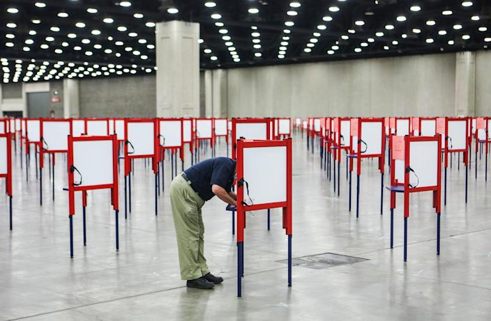 A man stands at a voting booth surrounded by many empty voting booths during early voting in Kentucky