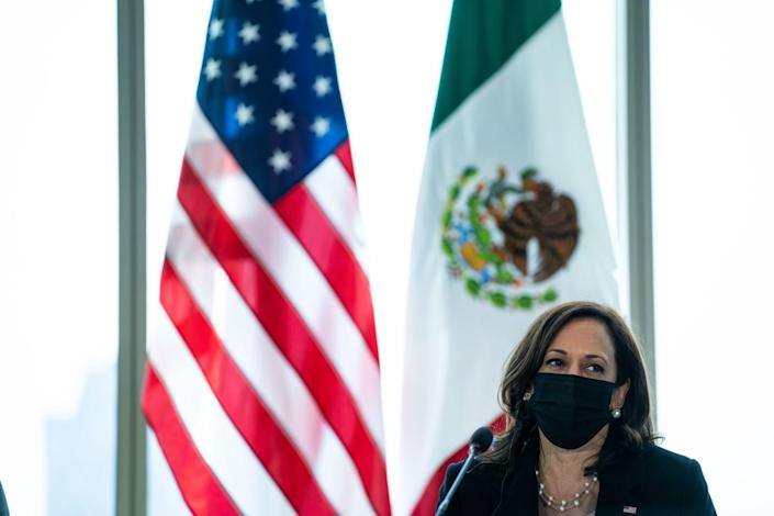 Vice President Kamala Harris, in a mask, with U.S. and Mexican flags in background