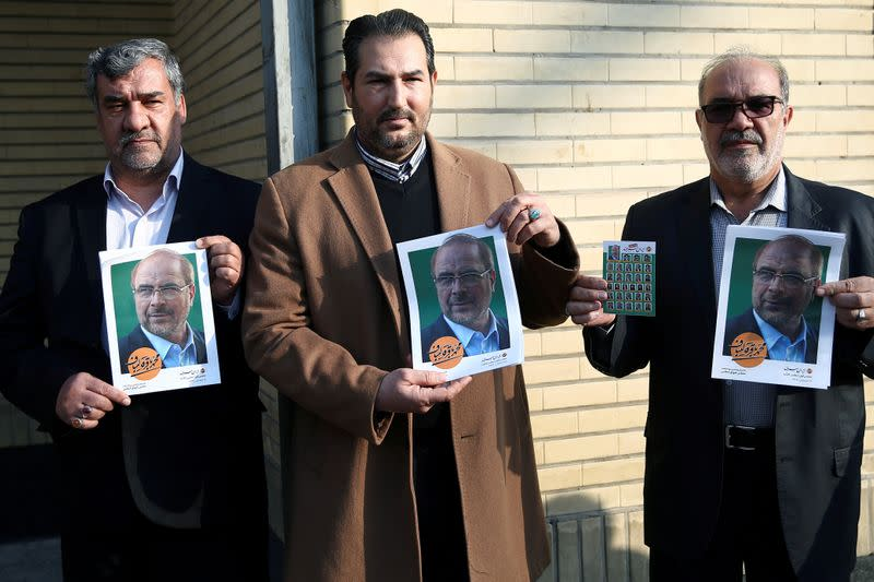 Iranian men hold posters of Mohammad Baqer Qalibaf one of parliamentary candidate in Tehran