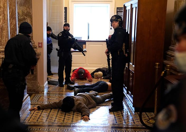 """U.S. Capitol Police detain pro-Trump rioters outside of the House Chamber of the U.S. Capitol on Jan. 6.<span class=""""copyright"""">Drew Angerer—Getty Images</span>"""