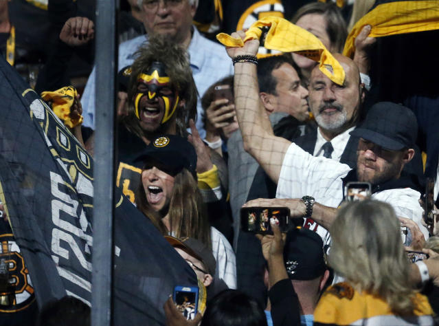 Olympian Ally Raisman, left, waves the Boston Bruins team banner as New England Patriots' Julian Edelman, right, twirls a towel before Game 7 of the NHL hockey Stanley Cup Final between the Bruins and the St. Louis Blues, Wednesday, June 12, 2019, in Boston. (AP Photo/Michael Dwyer)
