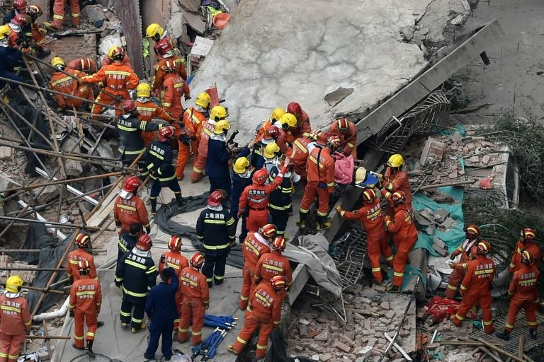 Rescue personnel pulled bloodied and dust-coated workers out from the rubble